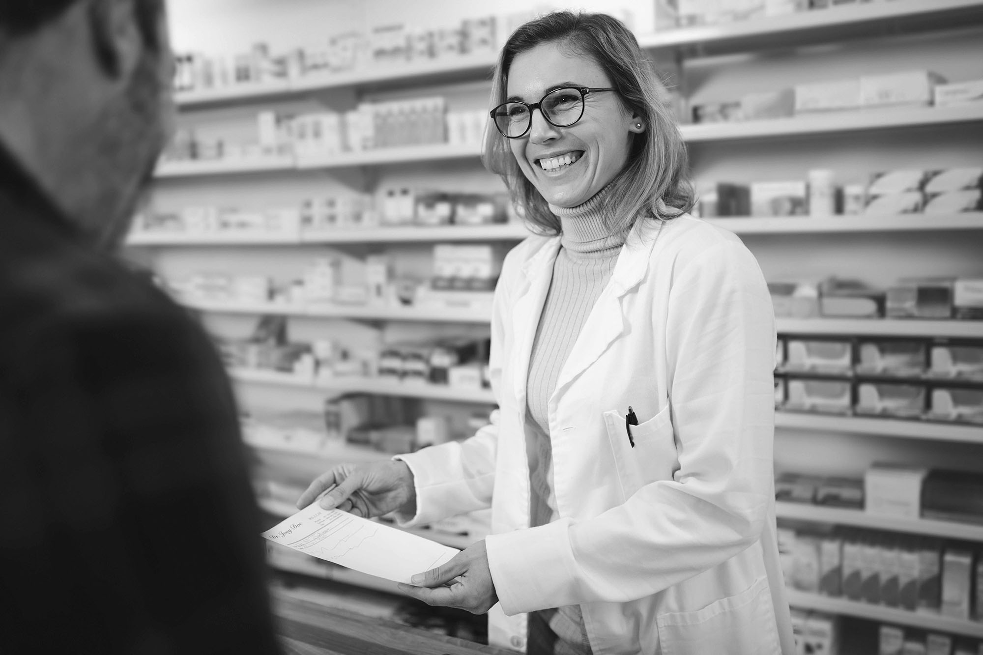 pharmacist gives prescription to customer